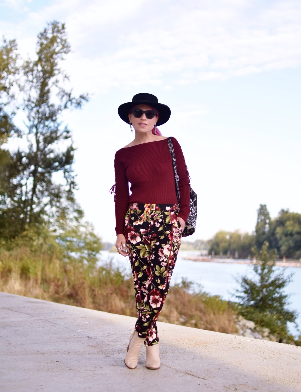 Monika Faulkner outfit inspiration - maroon sweater, floral trousers, ivory booties, flat-top fedora, cat-eye sunglasses