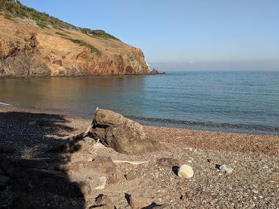 Spiaggia dei Mangain and the red Punta dei Mangani.