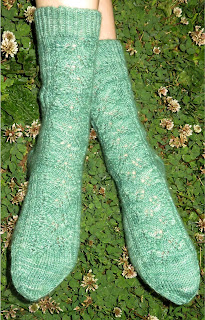 Someone wearing a pair of green socks. They have a lace leaf pattern along the leg and top of the foot