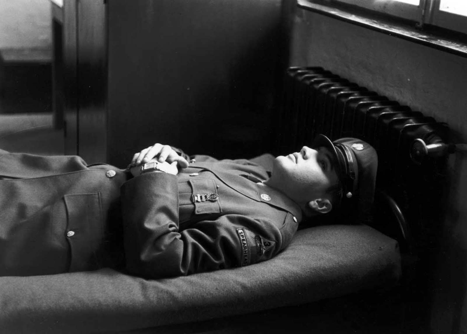 Elvis rests on an army cot.