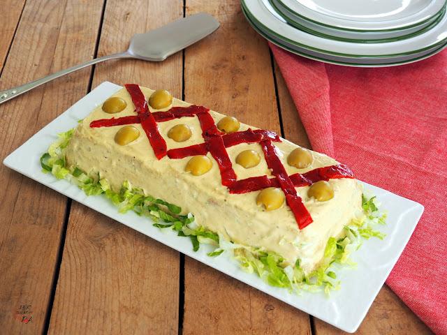 Pastel o sandwich de verano, a base de capas de pan de molde, lechuga, atún, anchoas, huevo duro, pimientos y olivas, aderezado con salsa de tomate y mayonesa de pepinillos.