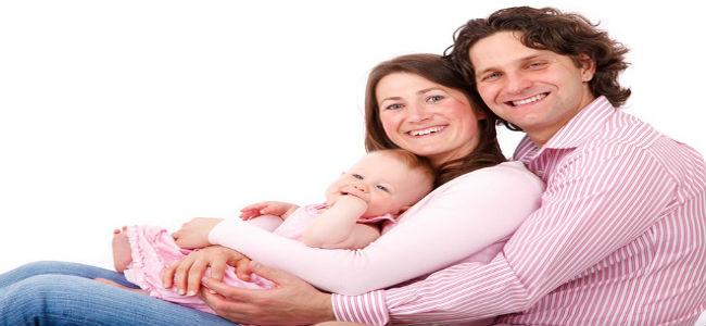 bebê no colo da mãe e mãe sendo abraçada por marido  e pai