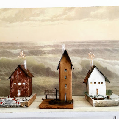 Three small assemblage-art houses on display in front of a picture of a stormy sea.
