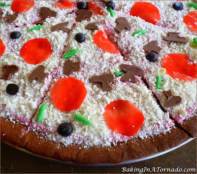 April Fools Peanut Butter and Jelly Pizza Cookie, a fun trick to play on the family. Peanut Butter Cookie, jelly in the frosting and lots of fun sweet toppings. | Recipe developed by www.BakingInATornado.com | #AprilFoolsDay #recipe #cookie