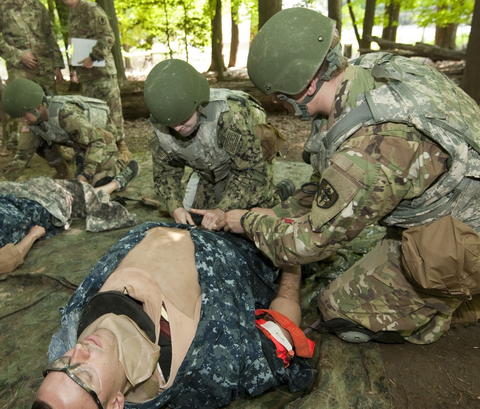 "First-year students assess a ""casualty"" wearing a cut suit simulator as part of a combat casualty care scenario during USU's Advanced Combat Medical Experience course. (Photo by Thomas Balfour)"