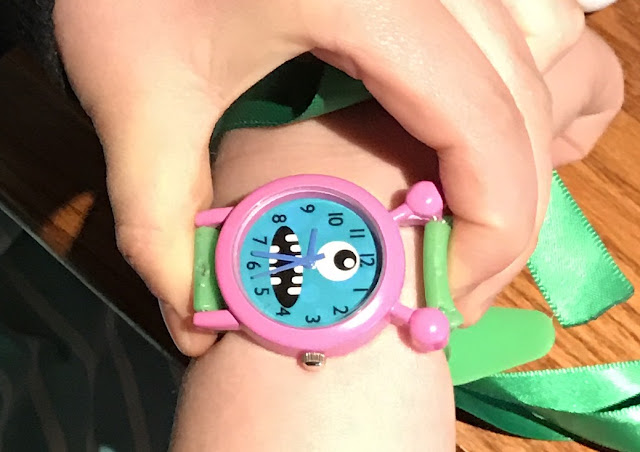 A close up of the watch face of the pink Furry Friends Watch. It has one eye and a big mouth