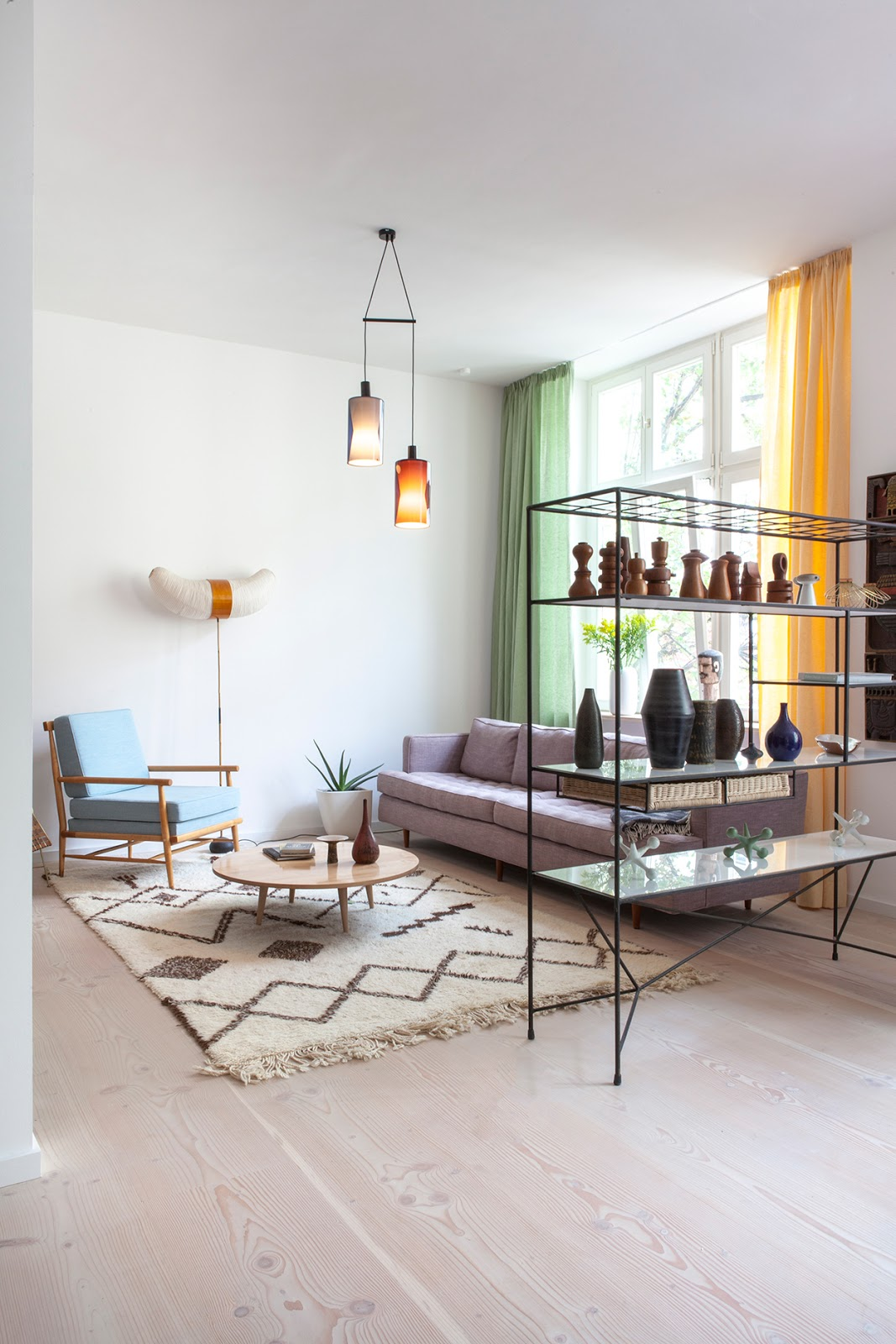 amazing designer loft in berlin with mdi century modern design, noguchi lamp, pattern carpet, pottery collection, light blue armchair