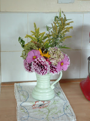 A green ceramic jug filled with flowers on a kitchen counter