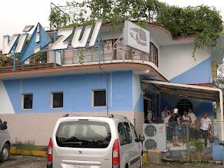 Kuba, Havanna, Viazulstation in Nueovo Vedado, bescheidenes Gebäude, davor wartet eine Gruppe Reisender.