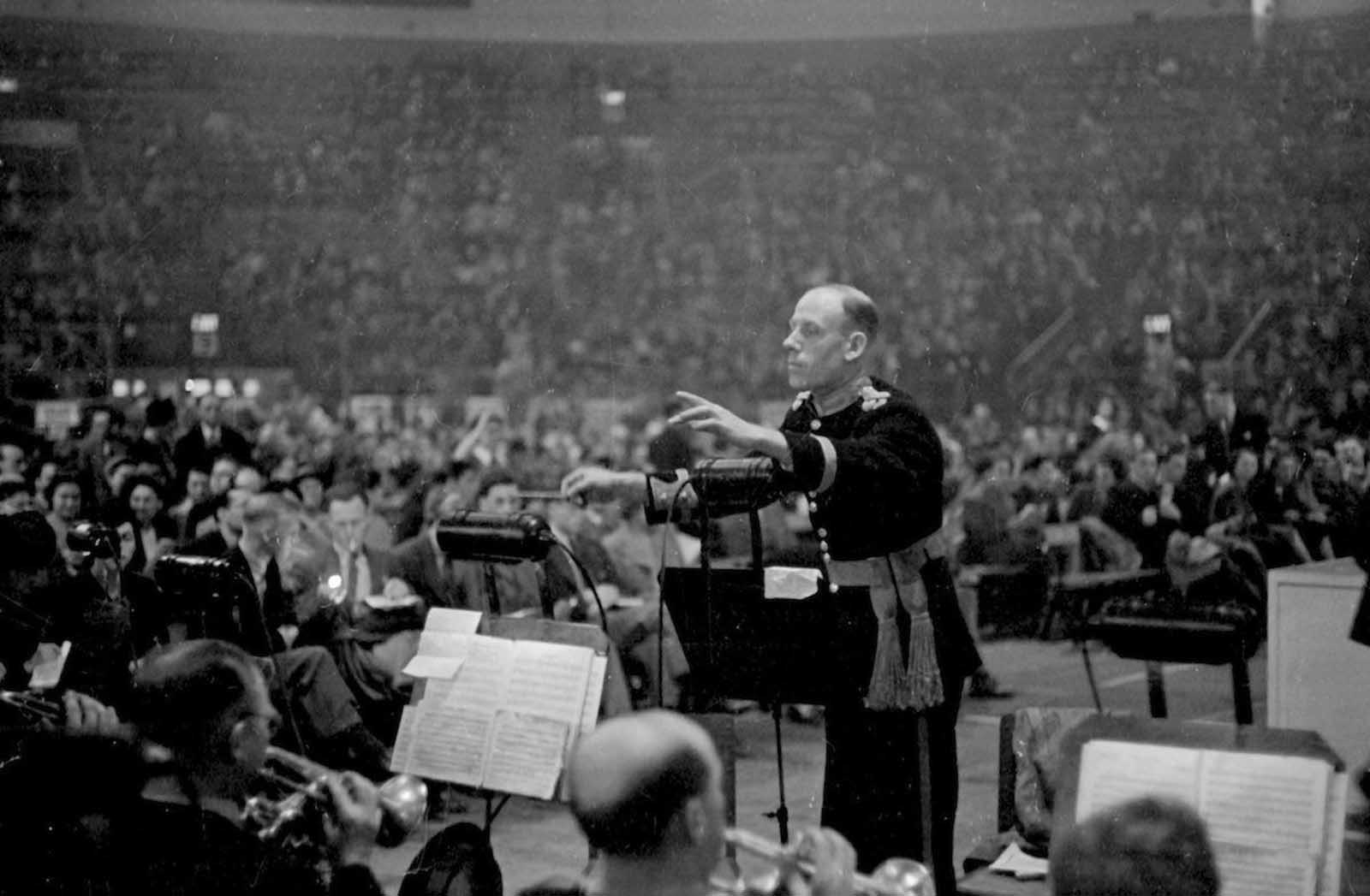 A band leader conducts his band at a meeting of the British Communist Party at the Empress stadium in Earls Court, London. 1939.