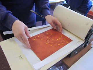 Photograph of student placing their inked board on the printing press