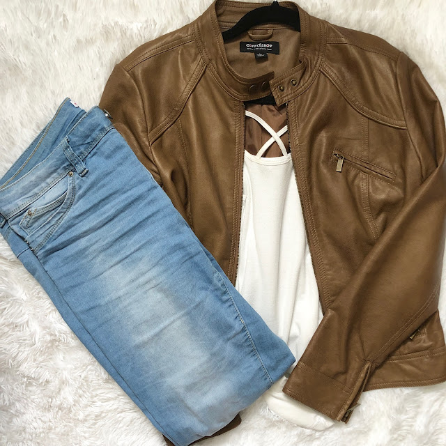 White cami with a brown leather jacket and light wash jeans
