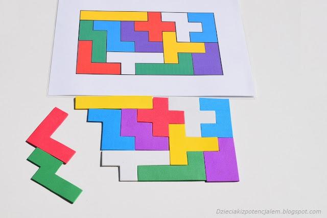 na zdjęciu kolorowa plansza z układem pentomino, pod nią leży prawie całkowicie ułożona układanka