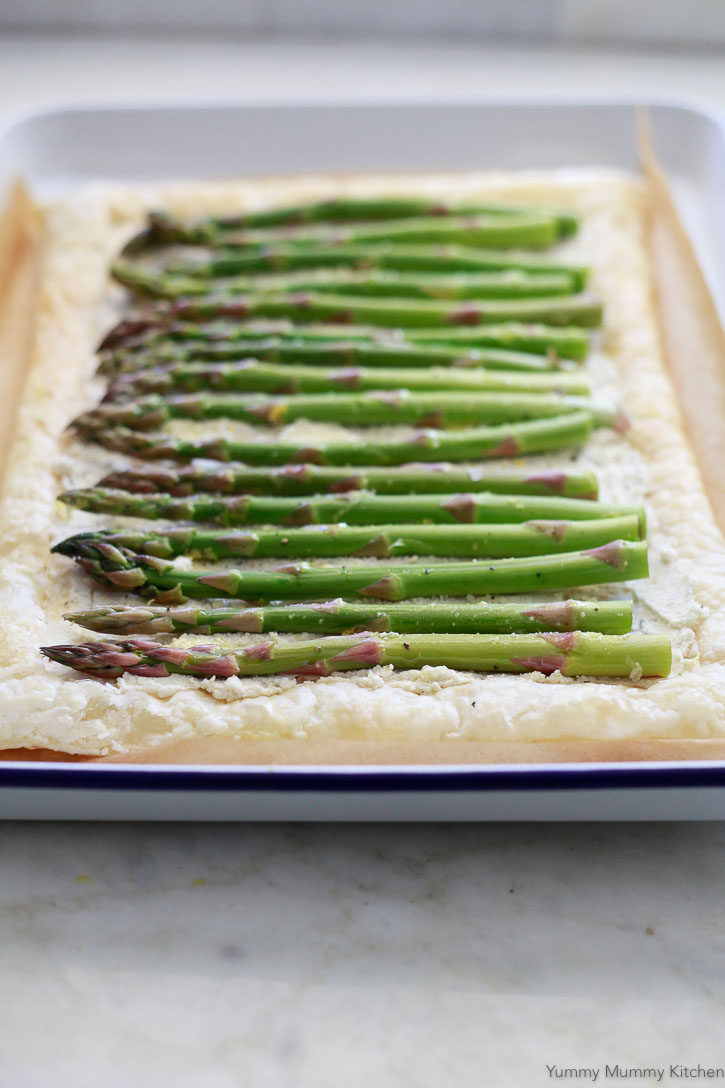 An easy asparagus tart with puff pastry, soft cheese, and seasoned asparagus on a white baking sheet ready for the oven.