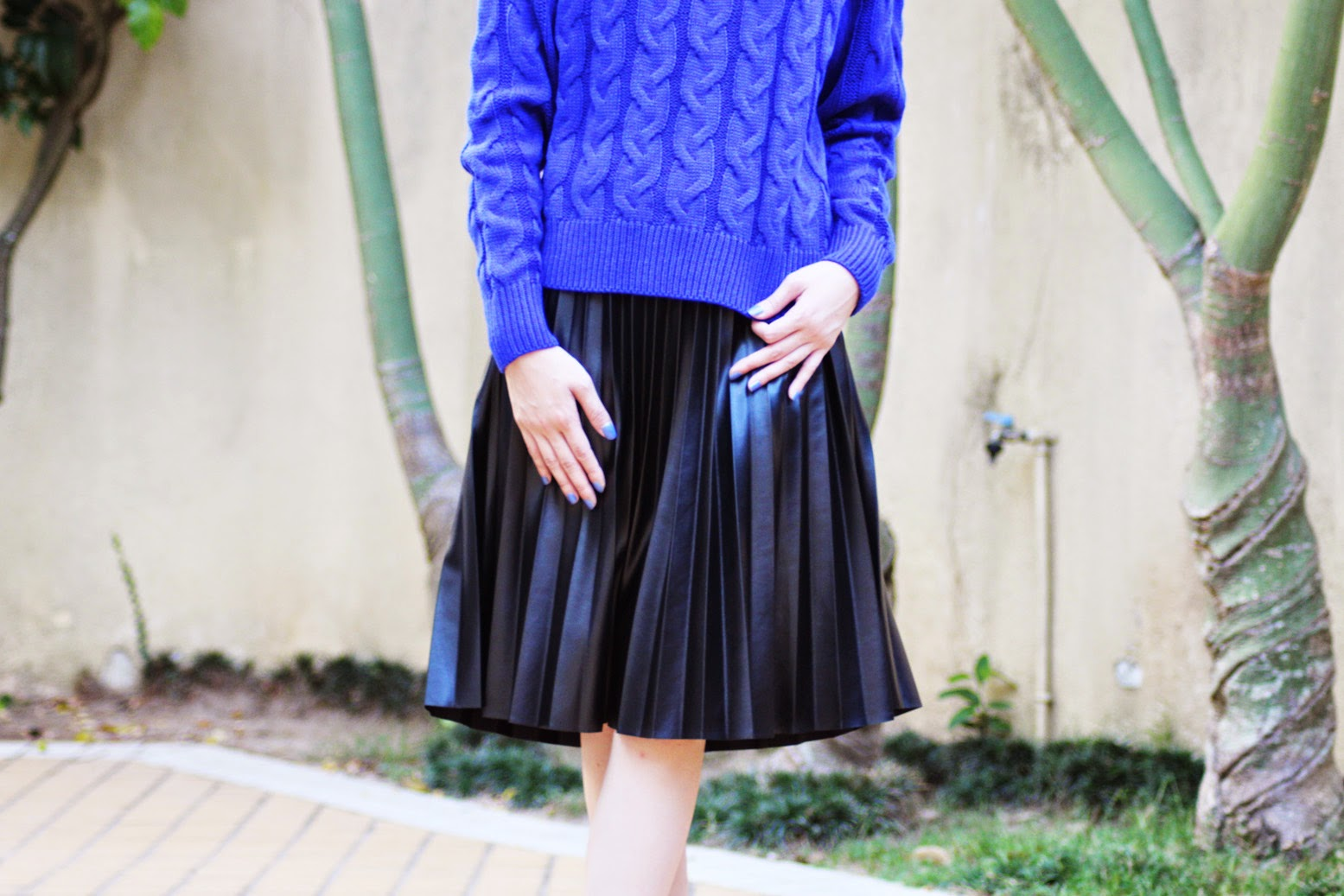 Styling blue sweater with black pleated faux leather midi skirt