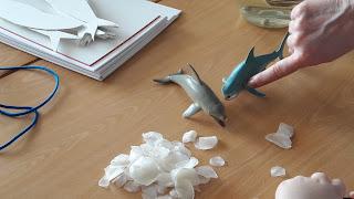 Em cima de uma secretária veem-se escamas brancas e um golfinho e um tubarão em plástico.