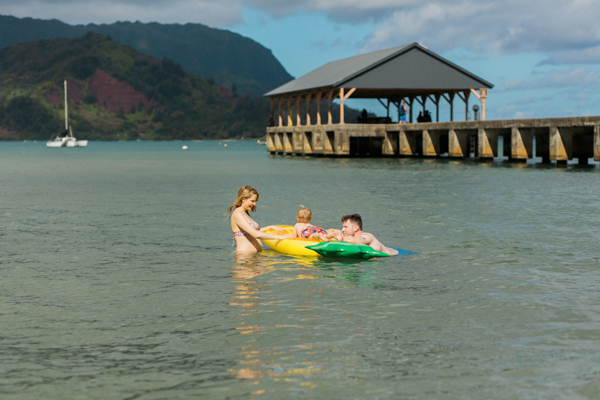 family of three, plus another on the way, in the water at Hanalei Bay, Kauai