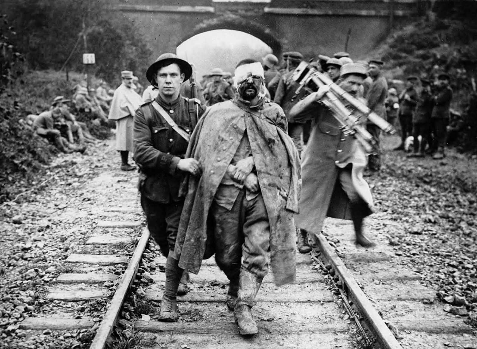 A German prisoner, wounded and muddy, helped by a British soldier along a railway track. A man, possibly in French military uniform, is shown behind them, holding a camera and tripod, ca. 1916.