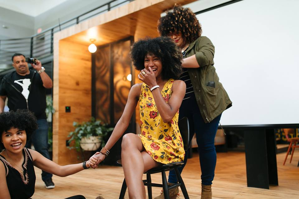 image: woman with curly hair cutting a girl's curly hair while crying happily. another girl holds the crying girl's hand while a man videotapes the experience in the background