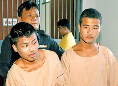 Zaw Lin (right) and Wai Phyo (left) being escorted by a Thai police officer.