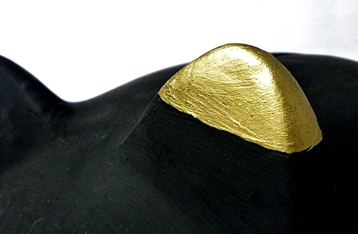 goldenes Ohr eines schwarzen Sparschweins