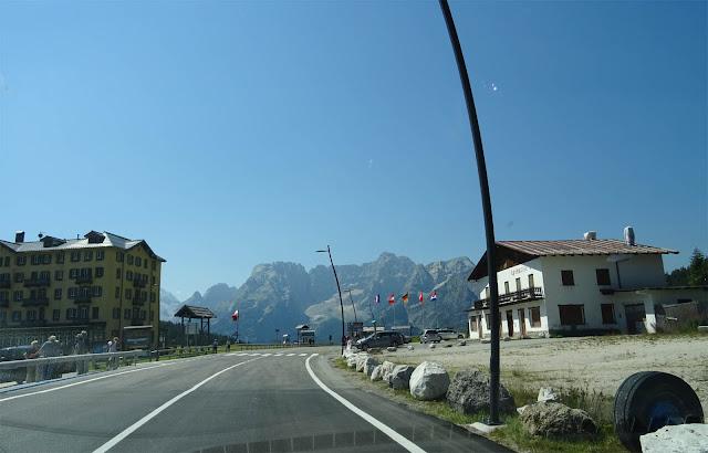 Gelb-braunes Haus, Bergmassive, blauer Himmel, Flaggen, Fahrbahn auf der Großen Dolomitenstraße in Südtirol
