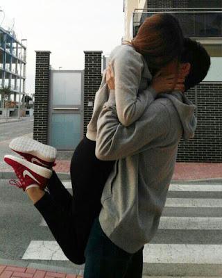pose de pareja en la calle cargandola