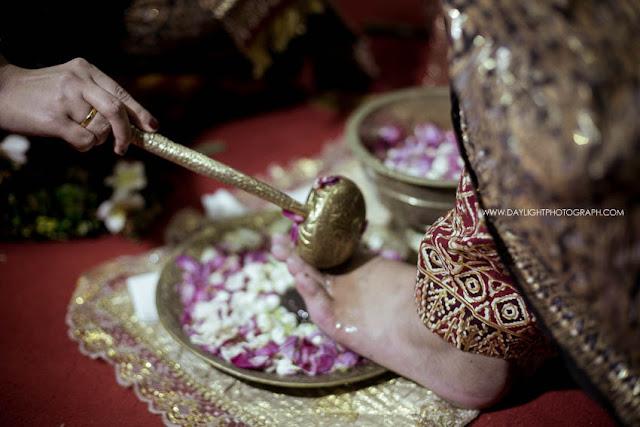 foto prosesi panggih, detail membasuh kaki pengantin laki laki dalam pernikahan tradional
