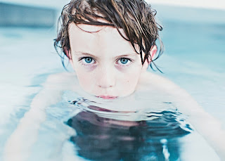 Young boy floating in water up to his chin, looking into camera with blue eyes.