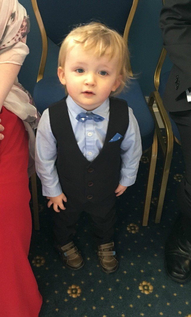 Toddler standing to attention dressed smartly for the wedding with waistcoat and bow tie