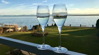 Twee glazen op de railing van het balkon en uitzicht op het water.