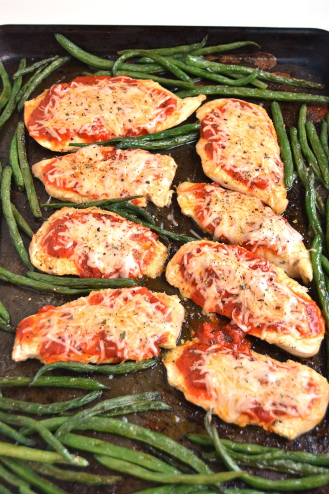 5-Ingredient Baked Chicken Parmesan cooks on a sheet pan and skips the breading and frying for a healthier meal! Loaded with your favorite tomato sauce and melted Parmesan and mozzarella cheeses. www.nutritionistreviews.com