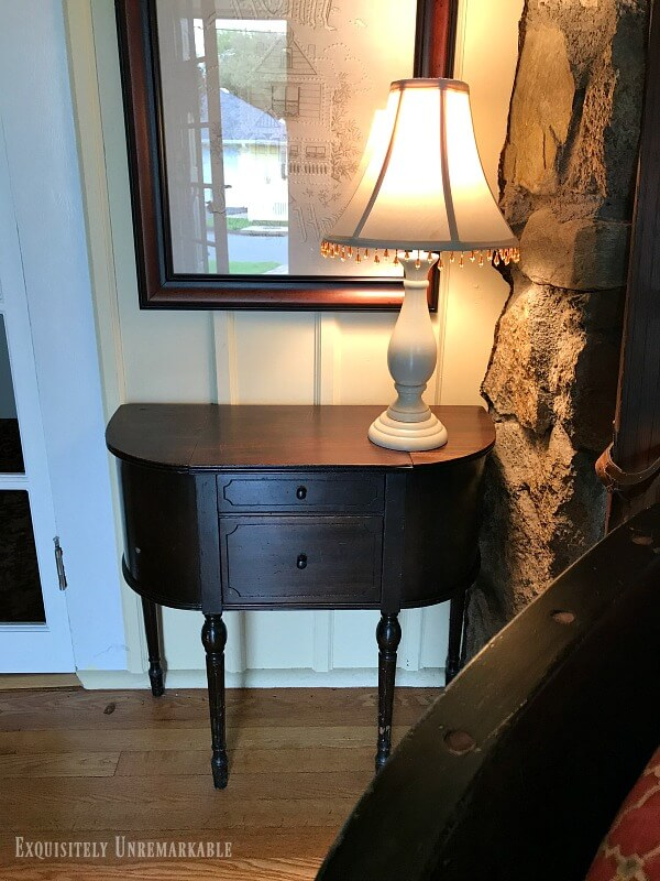 Small Vintage Sewing Table next to a stone fireplace