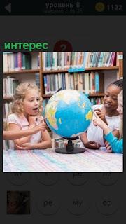 На столе глобус и дети его разглядывают, вращая вокруг собственной оси