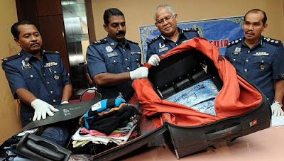 Malaysian immigration officers find drugs hidden in a passenger's luggage.