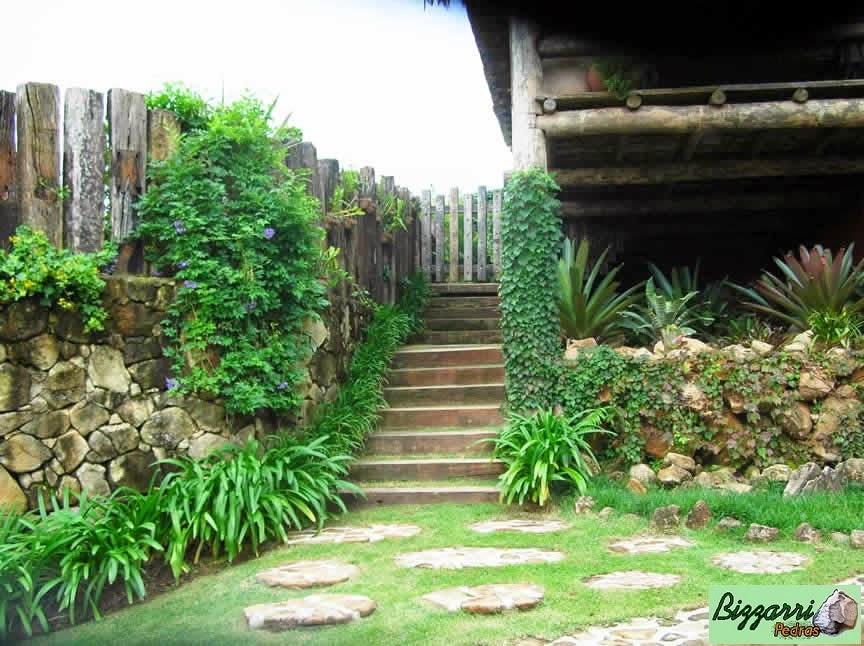Construção de muro de arrimo com pedra moledo com a escada de dormentes de madeira. De um lado o muro de pedra faceado e do outro lado o muro de pedra rústico.