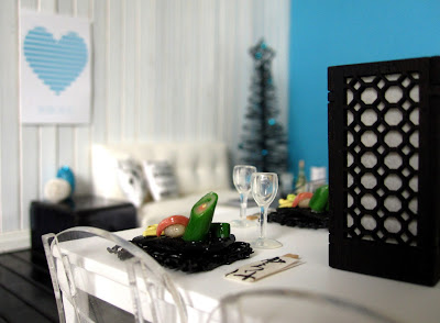Modern one-twelfth scale miniature scene in white and teal, showing two sushi meals on a table and a Christmas tree in the background.