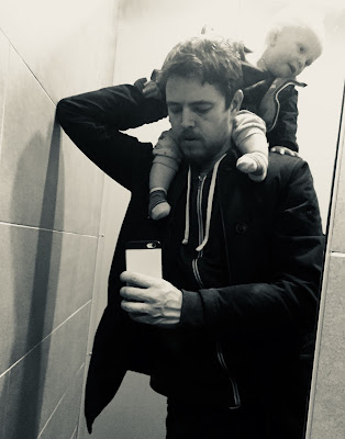 A picture of me looking frustrated in the toilet with my baby on my shoulders