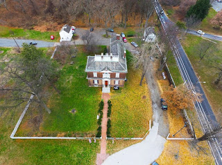 An aerial view of a mansion surrounded by trees