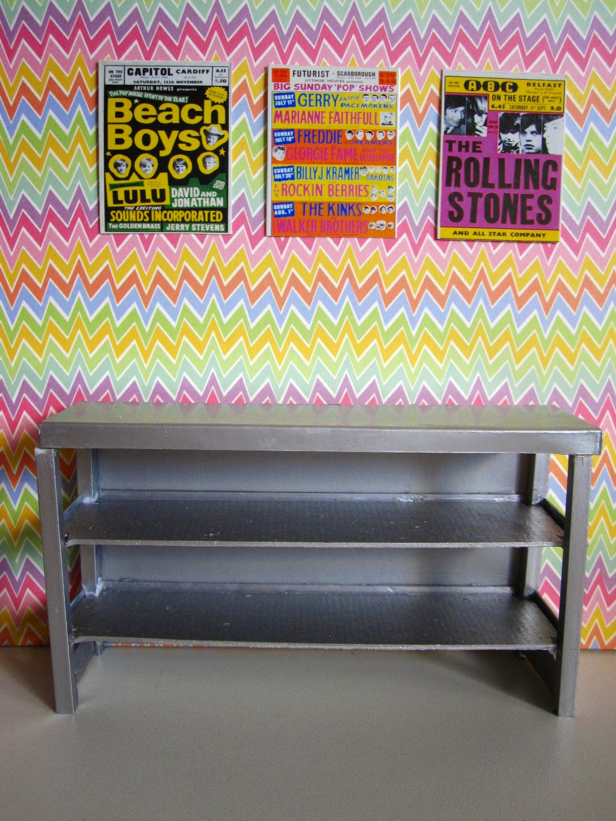 Selection of bright 1960s band posters arranged on a bright, zig zag-patterned wall. Underneath is a modern doll's house miniature industrial grey storage bench.
