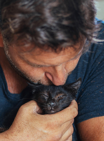 man kissing black kitten on the head