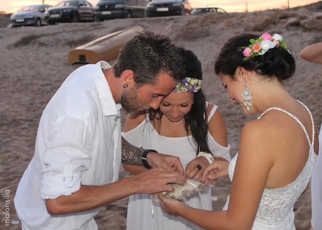Momento de la entrega de los anillo a los novios en una boda inicenca vestidos de blanco
