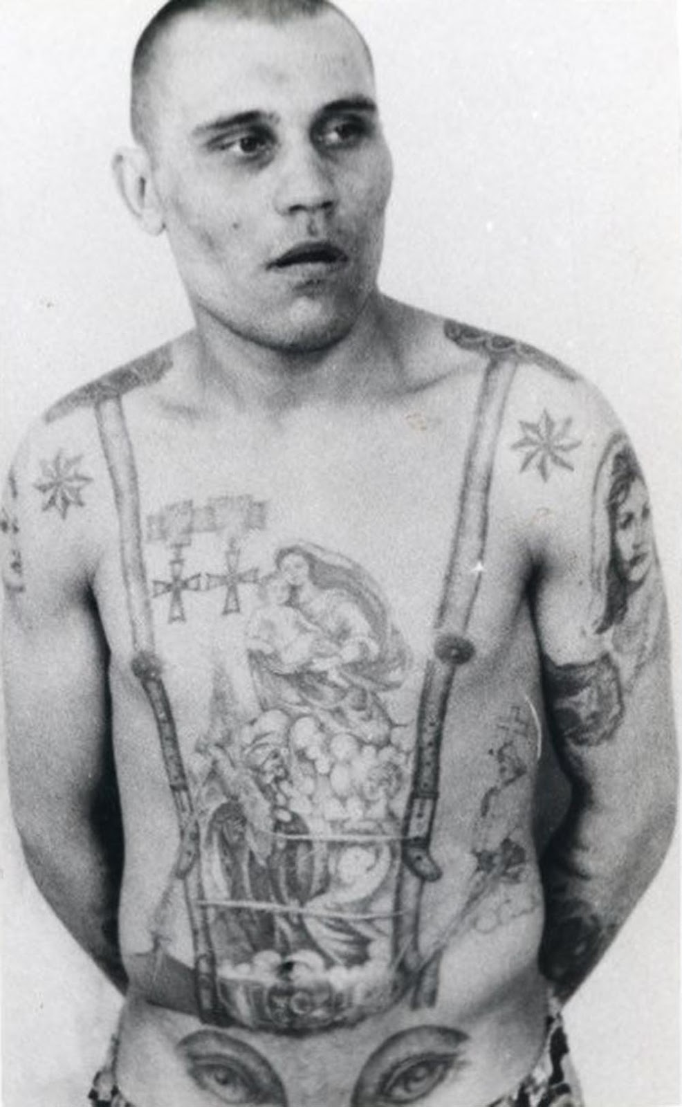 The stars on the shoulders show that this inmate is a criminal authority. The medals are awards that existed before the revolution and, as such, are signs of antagonism and defiance toward the Soviet regime. The eyes on the stomach denote a homosexual (the penis makes the 'nose' of the face).