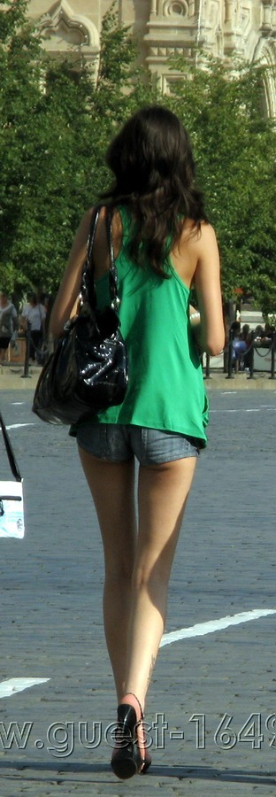 Tall slim brunette in a green tank shirt and denim ultra shorts
