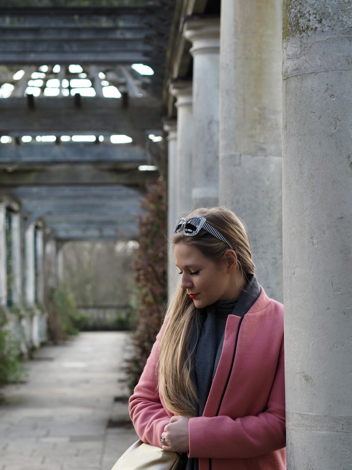 Blonde girl wearing pink coat leaning against pillar