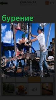 Двое рабочих на скважине занимаются бурением, вставляют трубу в механизм