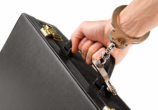Man's wrist handcuffed to a briefcase.