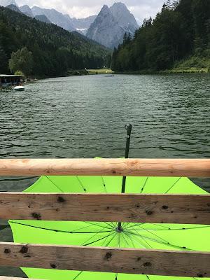 Sturm am See, grüner Schirm, Bunte Wiesenblumenhochzeit im Riessersee Hotel Garmisch-Partenkirchen, heiraten in Bayern, zwei Bräute, Regenbogen