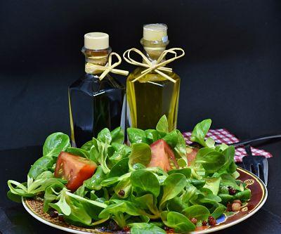 Ensalada verde en un plato. Contiene tomate, rúcula y panceta. Detrás se ven un frasco de aceite y uno de vinagre.