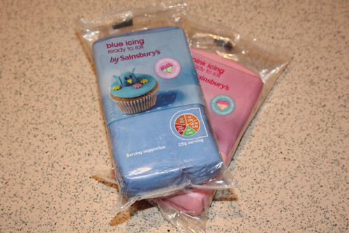 Sainsbury's ready to roll icing in blue, on top of a pink pack of the same icing